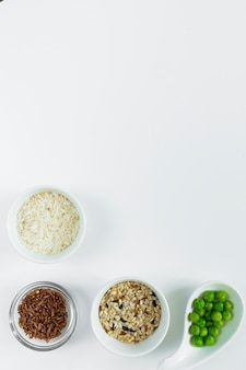 Different types of rice with green beans in bowls