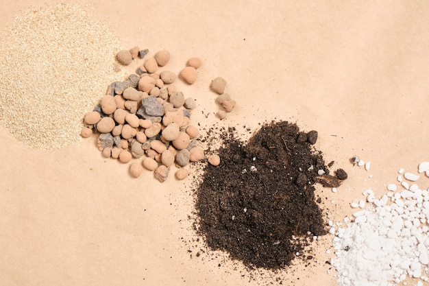 Different types of soil, soil additives and fertilizers on kraft paper, copy place, gardening concept copy space