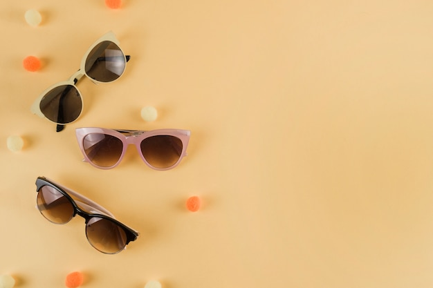 Different types of sunglasses with pom pom on beige backdrop