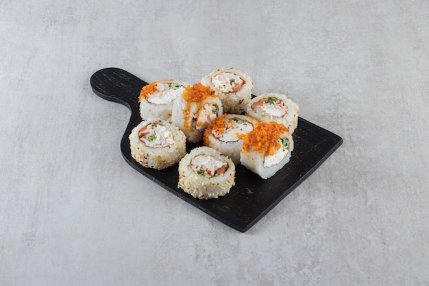 Different types of sushi rolls placed on a wooden board .