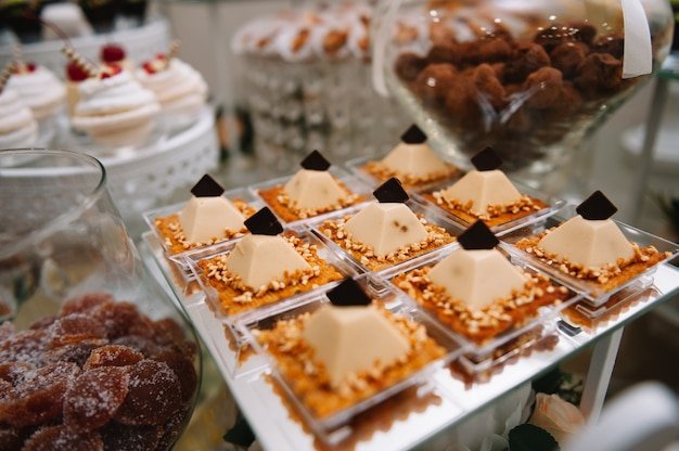 Different types of sweet pastries, small colorful sweet cakes, macaron, and other desserts