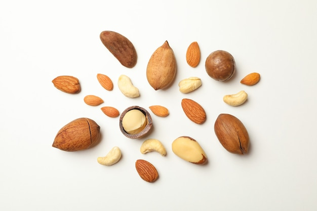 Different types of tasty nuts on white background