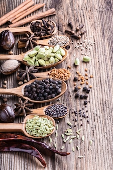 Different types of whole indian spices in wooden background close-up.