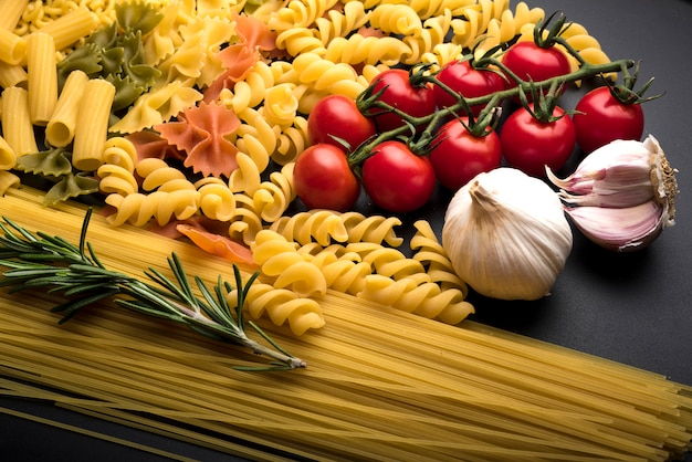 Different uncooked pasta with fresh ingredients