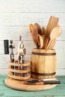 Различная посуда в деревянной бочке на цветном столе и деревянных досках