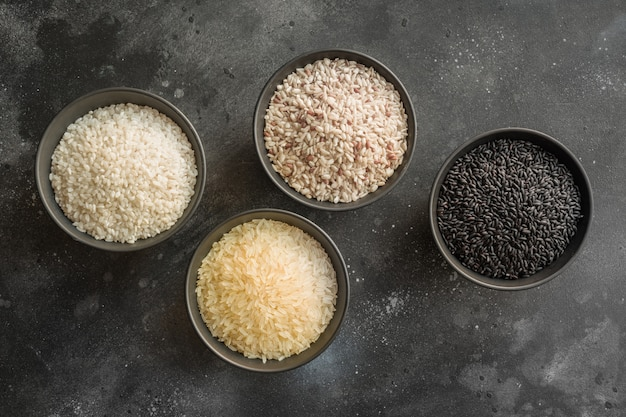 Different varieties of rice. black rice in bowl on black. top view.
