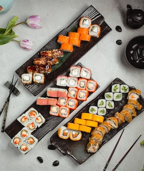 Different variety rolls with chopsticks on a black plate.