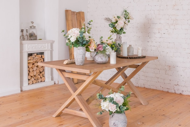 木製のテーブルの上に花が付いている別の花瓶