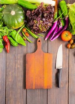 Различные овощи и пустая разделочная доска с кухонным ножом шеф-повара. приготовление концепции здорового питания. вид сверху. копировать пространство