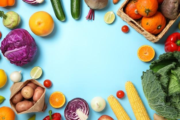 Разные овощи и фрукты на синем