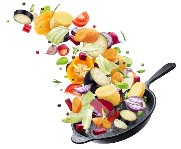 白い壁にフライパンに陥るさまざまな野菜