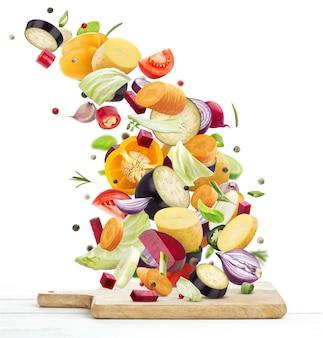 白で隔離の木製まな板に落ちるさまざまな野菜