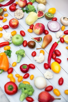 Different vegetables and fruits on a wooden background top view.