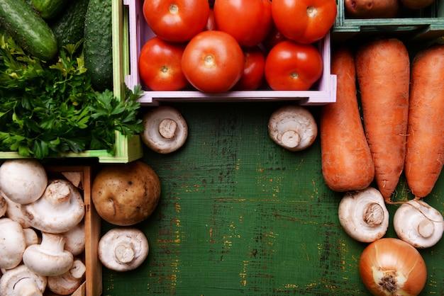 Различные овощи в ящиках на деревянном столе фоне вид сверху
