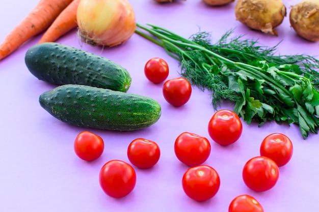 보라색 표면에 다른 야채, 야채-감자, 당근, 양파, 토마토, 오이 및 채소. 건강한 식단.