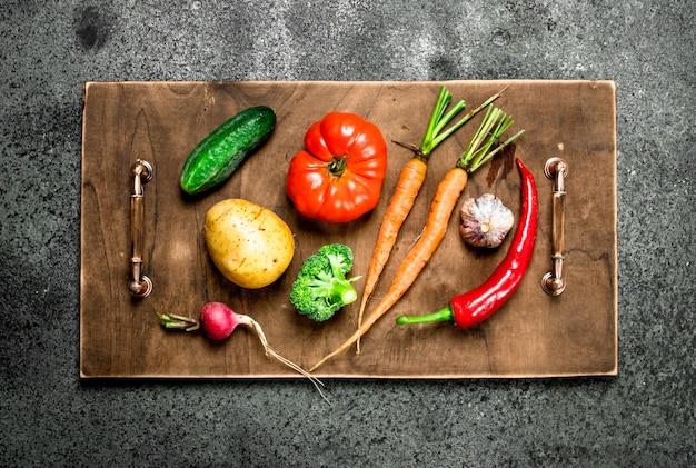 Различные овощи на деревянном подносе на деревенском столе.