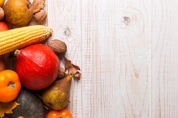 Different vegetables pumpkins, apples, pears, nuts, corn, tomatoes, dry yellow leaves on white wooden background. autumn harvest , copyspace.