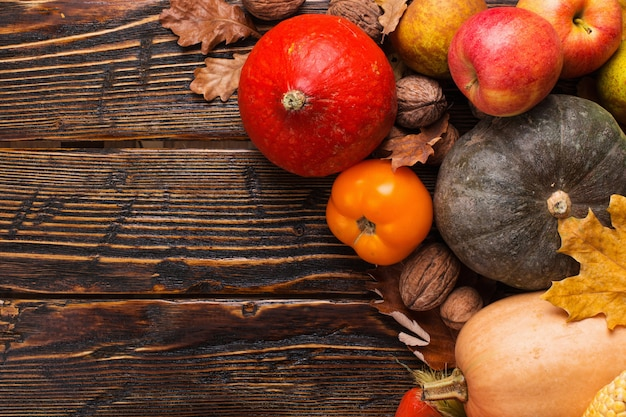 Different vegetables, pumpkins, apples, pears, nuts, tomatoes, corn, dry yellow leaves on wooden background. autumn mood, copyspace. harvest .