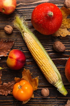 Different vegetables, pumpkins, apples, pears, nuts, tomatoes, corn, dry yellow leaves on wooden background. autumn mood, flat lay. harvest .