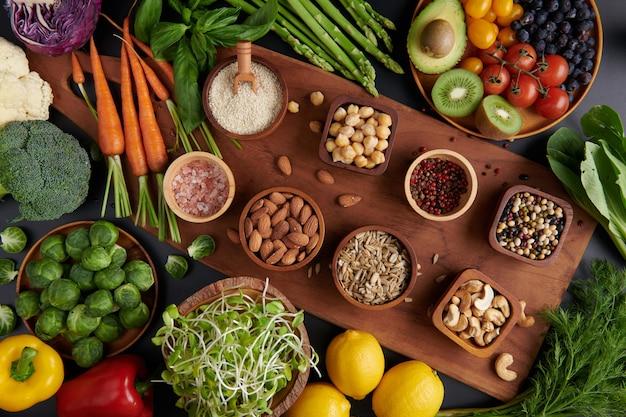 Различные овощи, семена и фрукты на столе. здоровая диета. квартира, вид сверху.