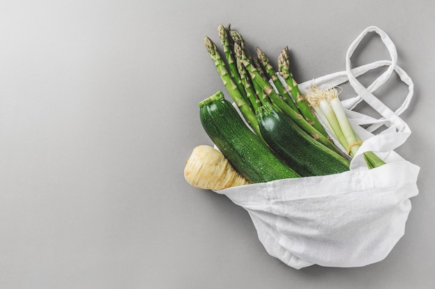 Different vegetables in textile bag on grey copyspace