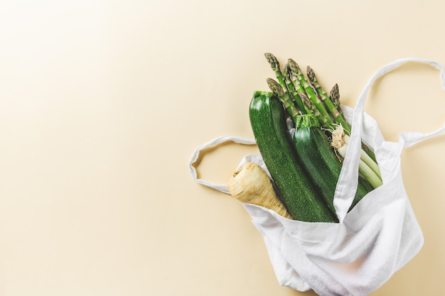 Different vegetables in textile bag on yellow copyspace