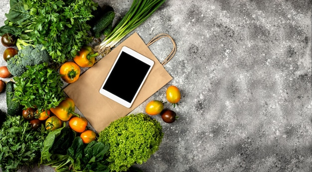 Different vegetables with tablet computer and shopping paper bag. banner top view with place for text.