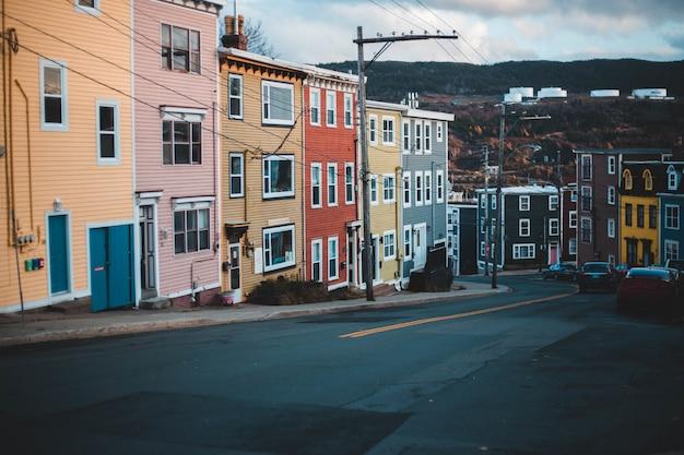 Различные автомобили на дороге возле разноцветных зданий под бело-голубым небом