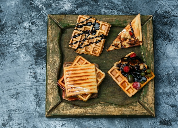 Different waffles on a bronze plate on a dark blue marble background. top view.