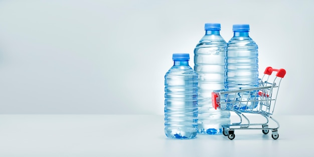 Different water bottle with shop trolley on gray background. banner. water delivery service concept.