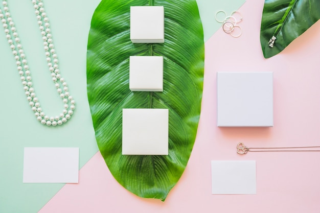 Different white boxes on green big leaf with jewelry on colored paper background