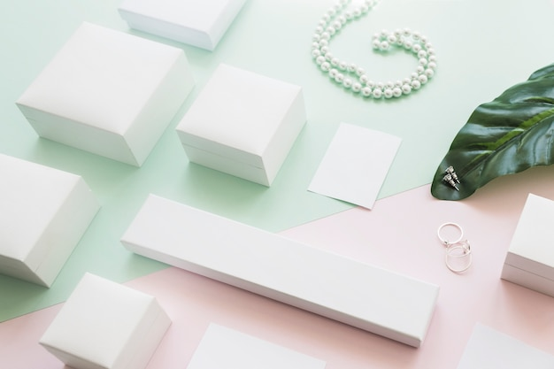 Different white boxes on leaf with jewelry on paper background