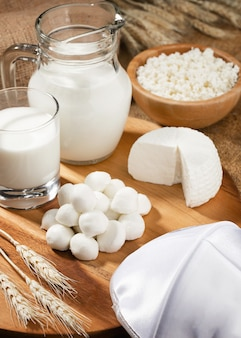 Различный белый сыр на деревянной подставке и колоски пшеницы.