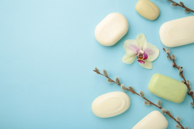 Different white soaps with flowers. a lot of solid soap for hygiene and cleanliness on a blue background. top view.