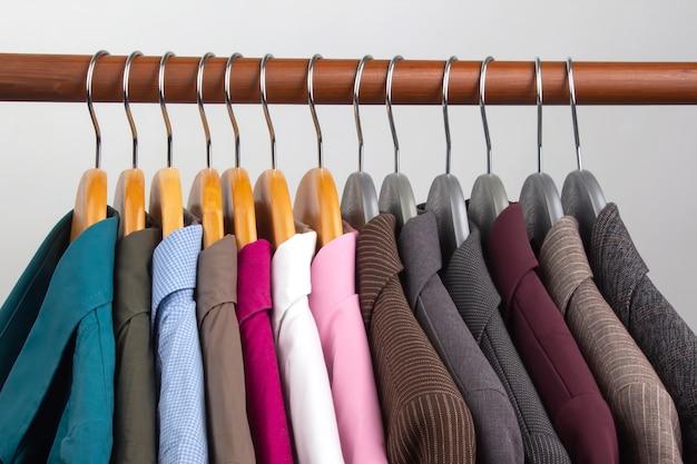 さまざまな女性のオフィスのクラシックなジャケットとシャツが、衣類を保管するためのハンガーに掛けられています。ファッショナブルな服のスタイルの選択