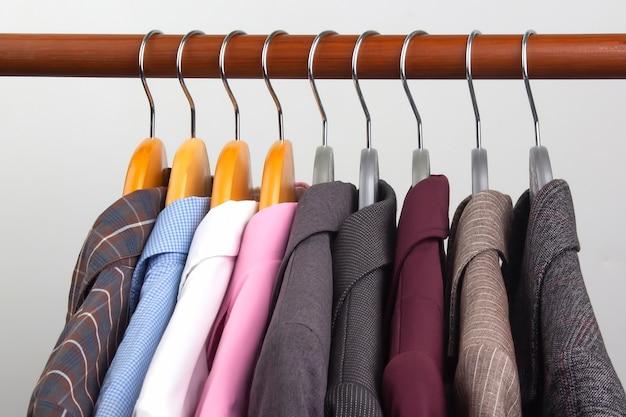 다른 여성용 사무실 클래식 재킷과 셔츠는 옷을 보관하기 위해 옷걸이에 매달려 있습니다. 세련된 옷 스타일 선택