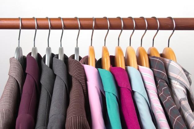 Различные женские офисные классические пиджаки и рубашки вешаются на вешалку для хранения одежды.