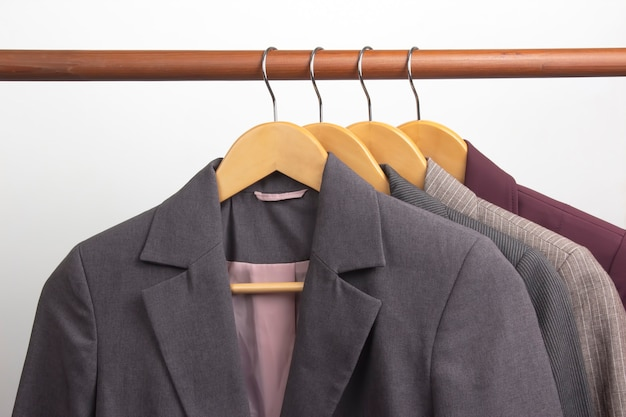 Different women's office classic jackets hang on a hanger for storing clothes. the choice of style of fashionable clothes
