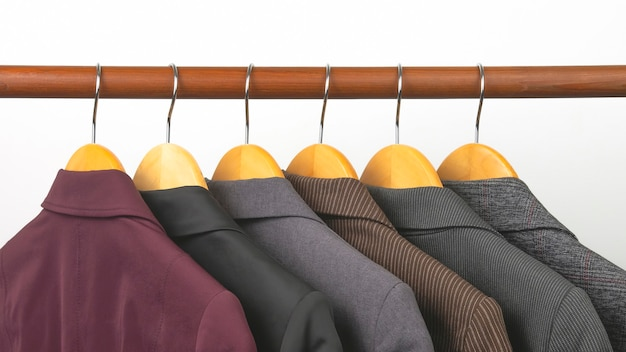 Different women's office classic jackets hang on a hanger for storing clothes