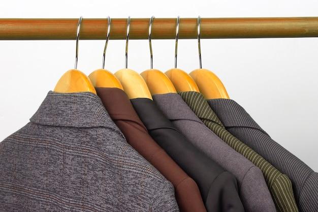 다른 여성용 사무실 클래식 재킷은 옷을 보관하기 위해 옷걸이에 매달려 있습니다. 세련된 옷 스타일 선택