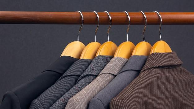 다른 여성용 사무실 클래식 재킷은 옷을 보관하기 위해 옷걸이에 매달려 있습니다. 세련된 옷 스타일 선택.