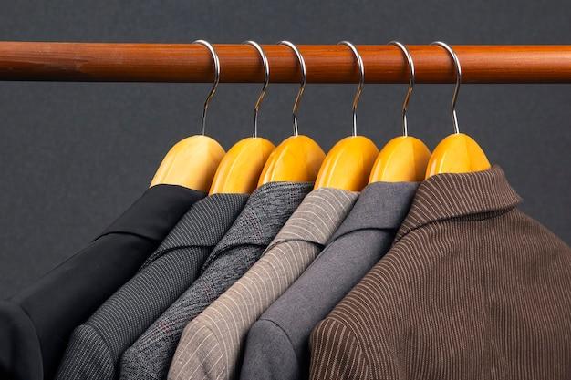 На вешалке для хранения одежды вешаются разные женские офисные классические пиджаки. выбор фасона модной одежды.