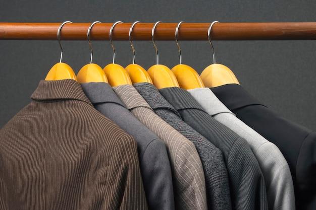 さまざまな女性のオフィスのクラシックなジャケットが、衣類を保管するためのハンガーに掛けられています。ファッショナブルな服のスタイルの選択。