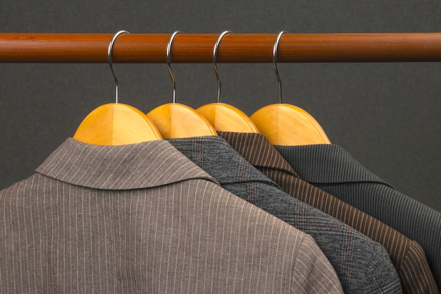 さまざまな女性のオフィスのクラシックなジャケットは、衣類を保管するためのハンガーに掛けられています。ファッショナブルな服のスタイルの選択