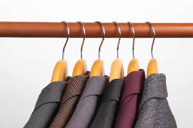 さまざまな女性のオフィスのクラシックなジャケットは、衣類を保管するためのハンガーに掛けられています。ファッショナブルな服のスタイルの選択。