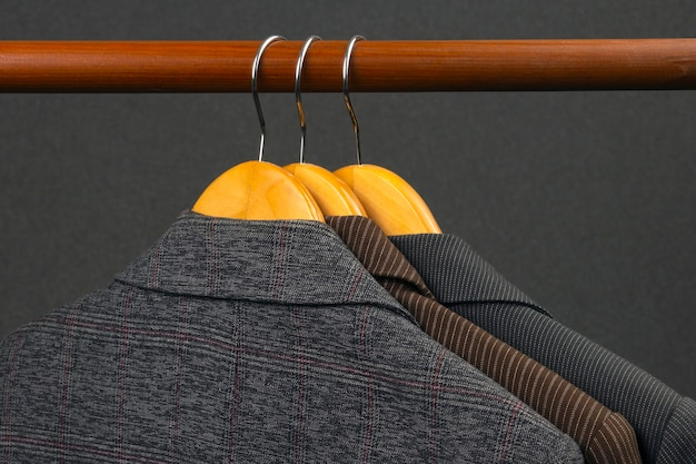 Различные женские офисные классические куртки вешаются на вешалку для хранения одежды.