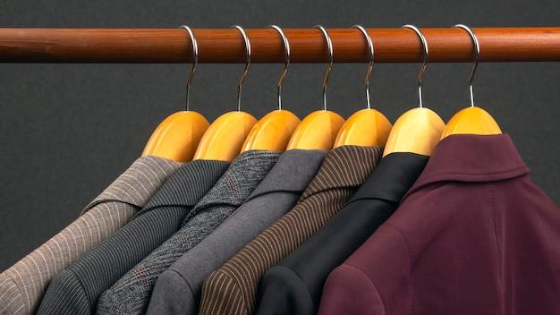 さまざまな女性のオフィスのクラシックなジャケットは、衣類を保管するためのハンガーに掛けられています。