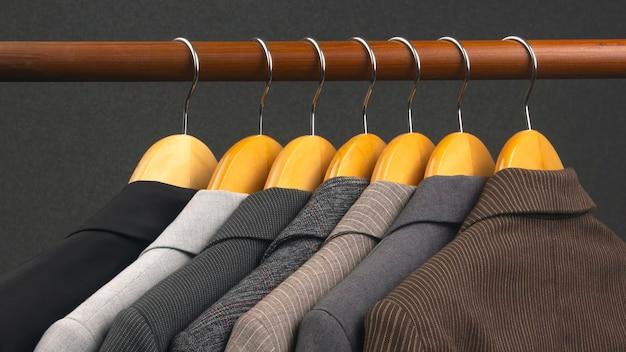 さまざまな女性のオフィスの古典的なジャケットは、服を保管するためのハンガーに掛かっています