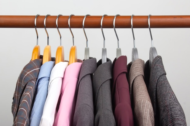 Different women's office classic jackets and shirts hang on a hanger for storing clothes.