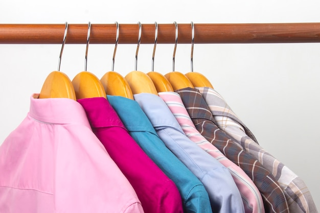 Different women's office classic shirts hang on a hanger for storing clothes.